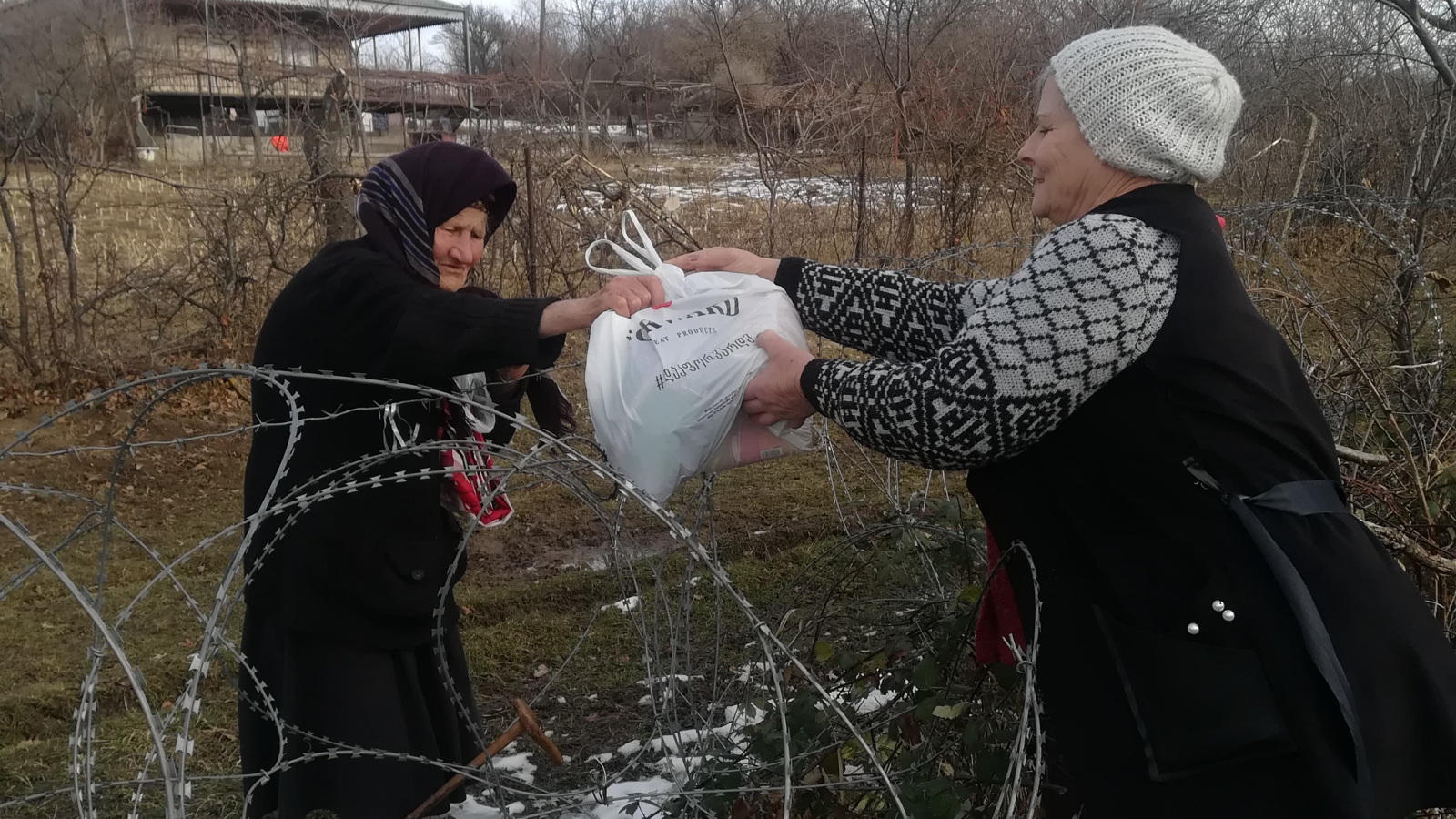 Galina Natela handing over masks to the people living near administrative border line