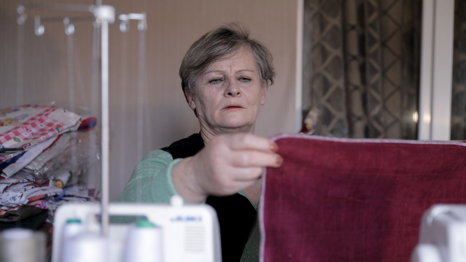 Galina Natela measuring the fabric during process of sewing linen